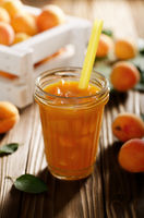 Apricot smoothie in mason jar on wooden table with crate at background