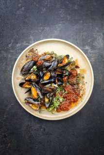 Traditional barbecue Italian blue mussel in tomato sauce with parsley and garlic in red wine sauce as top view on modern design plate with copy space