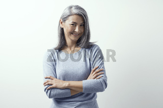 Beautiful Asian with white hair smiling standing near the wall