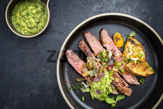 Modern Barbecue dry aged wagyu flank steak with pineapples and chimichurri sauce as top view on a plate