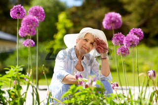 tired senior woman with flowers at working garden