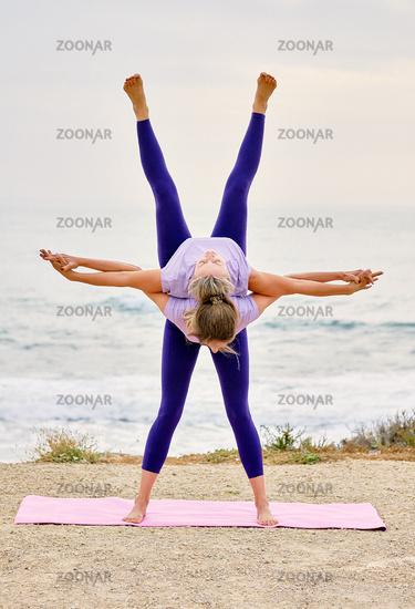 Women doing partner tandem yoga exercise standing on mat outdoors