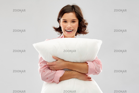 happy young woman in pajama hugging pillow