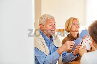 Gruppe Senioren beim Kartenspiel zu Hause