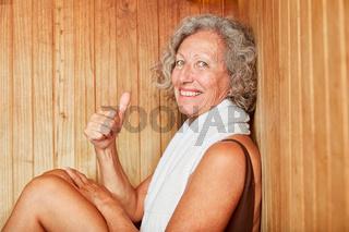 Frau in der Sauna mit Daumen hoch