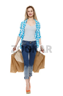 Front view of a woman walking with shopping bags.