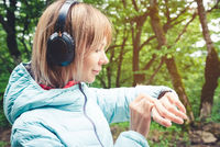 Portrait Young fitness woman looking at her smart watch while taking a break from sports training. Sportswoman checking pulse on fitness smart watch device in forest.