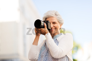 senior woman photographing by digital camera