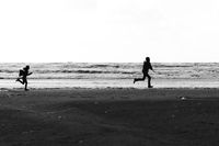 Silhouettes of a brother and a sister running wild and free at the beach