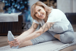 Smiling mature woman is touching her toes