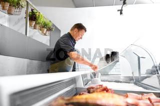 male seller adding ice to fridge at fish shop