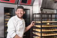 Smiling Baker putting a rack of pastries into the oven in bakery or pastry shop.
