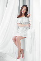 Young alluring woman dressed in white dress.