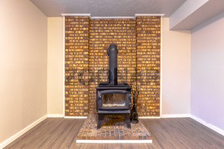 Fireplace intalled on a brick platform and against the stone brick accent wall
