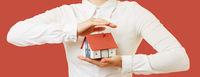 Hände halten Haus als Hausratversicherung Konzept