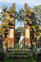 Young blonde caucasian woman traveling and exploring traditional hidu tamples around Ubud on Bali.