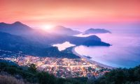 Panoramic landscape with blue lagoon, sea, city lights, mountains