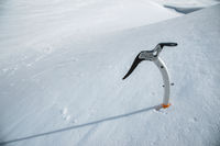 Close-up of an ice ax in the snow with snow-capped mountains in the background