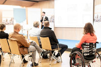 Rear view of nrecognizable woman on a wheelchair participating at business conference talk.