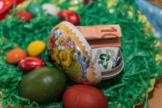 buntes Osternest mit gefärbten Eiern und Geldgeschenk