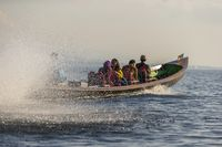 Long tail canoe full of tourists whizzing fast on Inle Lake, Myanmar