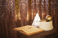 Little box with a lot of Christmas silver and golden decorations near the Christmas tree lamp and the book
