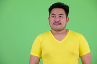 Face of young handsome overweight Asian man thinking