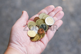 handful of small loose pocket change euro cent coins in palm of hand