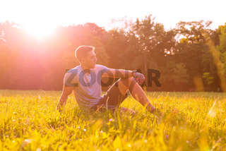 A young man sitting in the Grass