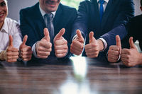Businessmen holding big thumbs up in a row