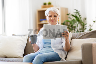 senior woman with coffee reading newspaper at home