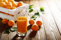 Apricot smoothie in glass on wooden table with crate at background