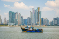 Old fisher boats in front of modern skyscraper city skyline in Panama City