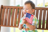Young Mixed Race Chinese and Caucasian Boy Playing With American Flag