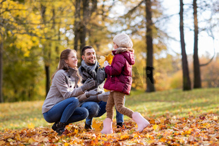 happy family with maple leaves at autumn park