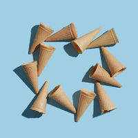 The pattern of wafer ice cream cones empty with shadows on a pastel blue paper. Flat lay.