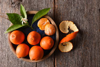 Closeup of peeled fruit on a plate with leaves and orange blossom on a rustic wood table