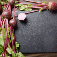Top view at fresh organic beets with leaves on wooden rustic table close up view