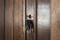 Old rusty keys inside a keyhole of an old antique closet. vintage design