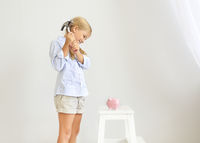 Little girl with hammer by the pink pig piggy bank