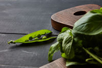 Pea pod and basil leaves on a wooden board on a dark wooden background