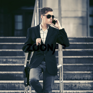 Young handsome business man calling on cell phone in city street