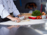 chef preparing dough for pizza with rolling pin