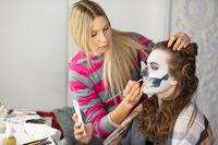 Makeup artist puts body art of a cute model