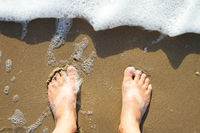Male feet standing on the beach watching the water waves from above.