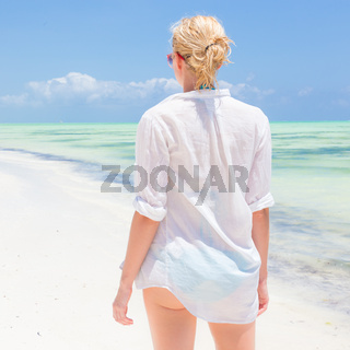 Happy woman enjoying, relaxing joyfully in summer on tropical beach.