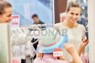 Mutter und Kind beim Hut Kauf in Boutique