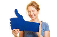 Junge Frau hält blauen Daumen hoch als Like