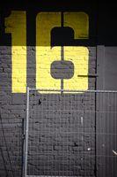 Gelbe Gebäudenummer auf dunklem Backstein