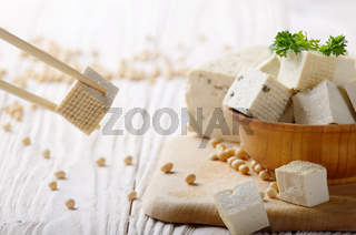Soy Bean curd tofu in wooden bowl on white wooden kitchen table. Non-dairy alternative substitute for cheese. Place for text
